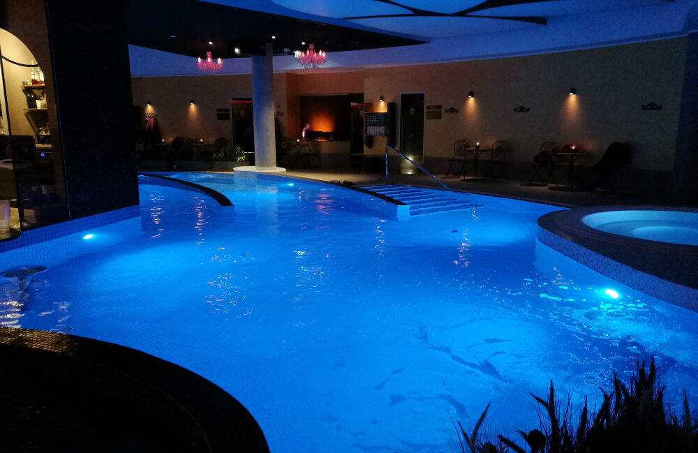 Kylpylän iso uima-allas, joka on valaistu sinisellä valolla.